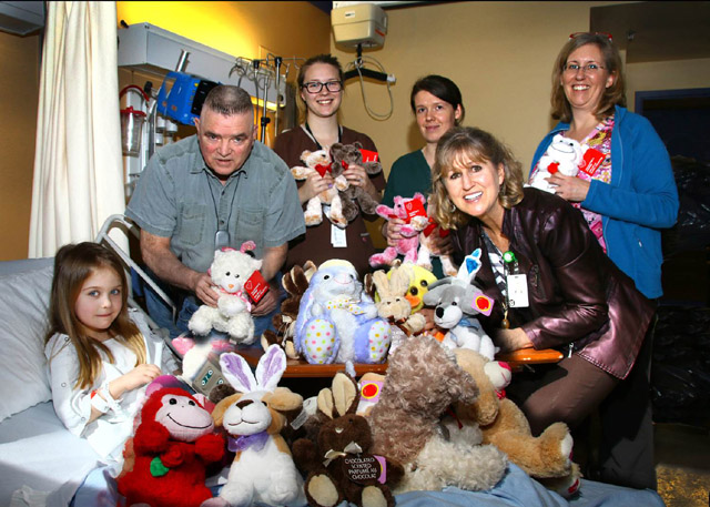 Stuffed animals donated by Ron Fortin (top left) help comfort a young patient in St. Joseph's Hospital's Maternal Child Unit with staff and our Hospital Foundation's Lynn Dashkewytch. Fortin has been donating toys and teddies to children at St. Joseph's Hospital for over 30 years (photo by Jim Peacock).