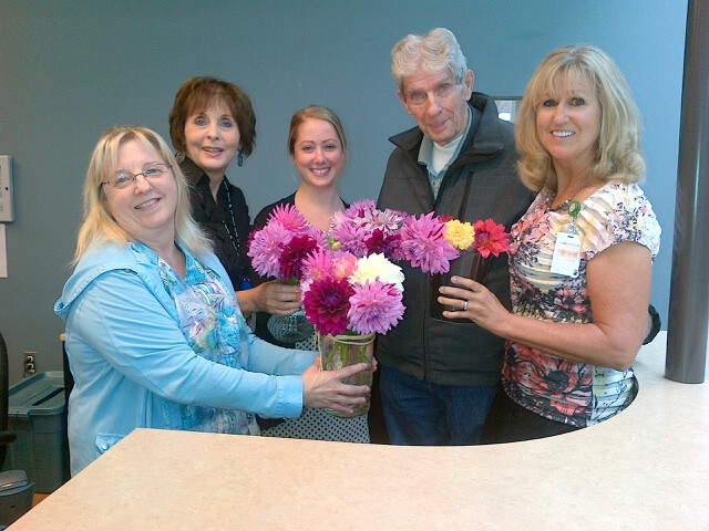 "Lorne Millar (aka ""The Dahlia Man"") has been bringing his basket of flowers to St. Joseph's Hospital twice a week for 28 years. Here he is seen with some of the hospital's front desk staff, as well as Lynn Dashkewytch from the Foundation."