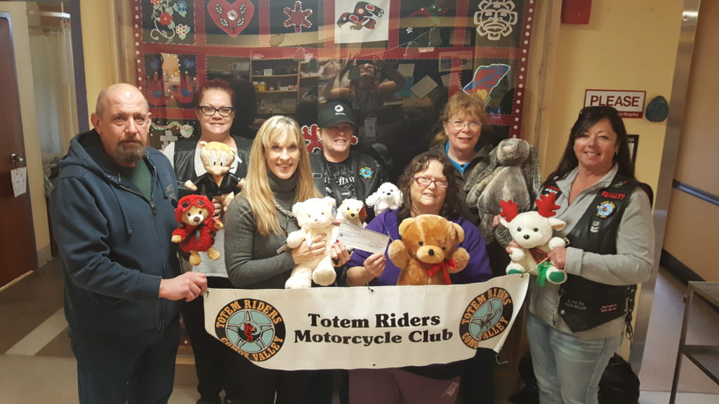 Members of the Totem Riders Motorcycle Club present the teddy bears and donations they raised at their Halloween Howl last October for Maternal Child Unit at St. Joseph's Hospital to Meghan Liddle of Comox Valley Healthcare Foundation.